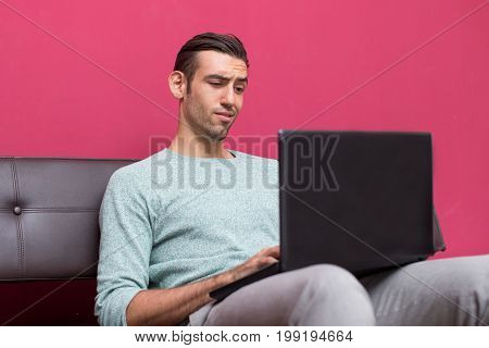 Closeup portrait of young man sitting on sofa, working on laptop computer and looking at screen with distrust at home