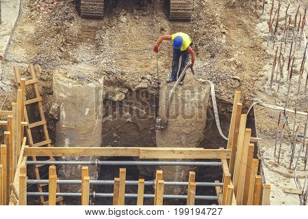 Worker Placing Water Pump To Drain Trench 2