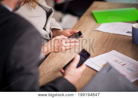 Business team meeting at modern work space. Close up view of man and woman coleagues holding smartphones in their hands.