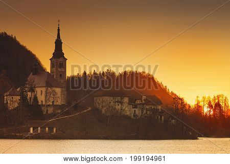 Amazing view on Bled Lake on sunrise. View on Island with Catholic Church. November morning on the lake at dawn. Autumn in Slovenia Europe.