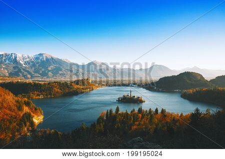Morning on Bled Lake at dawn. Autumn or Winter in Slovenia Europe. Top view on Island with Catholic Church in Bled Lake with Castle and Alps in Background.
