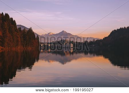 Amazing view on Bled Lake on sunrise. View on Bled village with snowy Alps on background. December morning on the lake at dawn. Autumn Winter in Slovenia Europe.