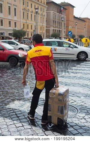 VATICAN CITY VATICAN - OCTOBER 18 2016: Unknown DHL courier with large package close to St peter's basilica
