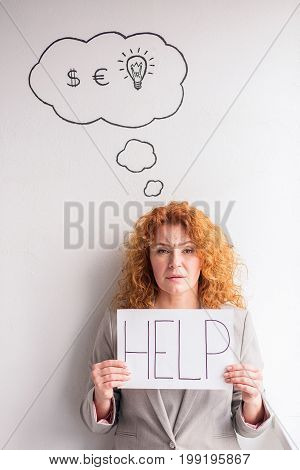 Dissapointed mid aged business woman holding poster with word HELP. Stressed tired woman needs asking for help.