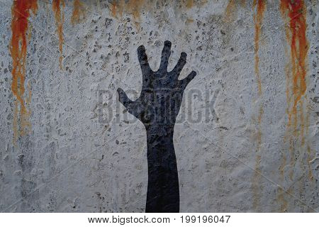 Shadow of right corpse hand on concrete wall with blood drops background. Zombie theme illustration.