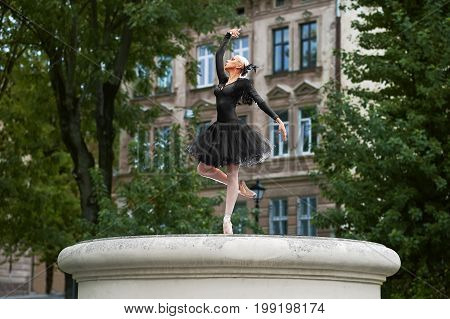 Gorgeous young graceful ballerina posing elegantly while performing outdoors in the town.