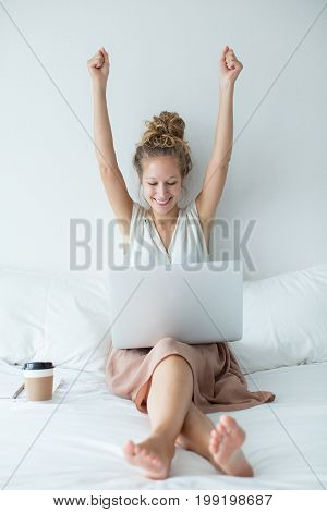Portrait of happy young Caucasian businesswoman sitting on bed, working on laptop and raising arms in joy
