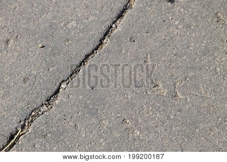 Texture with cracks on the asphalt background