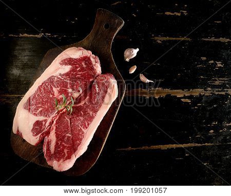 Raw fresh marbled meat Black Angus Steak and rosemary on dark wooden background