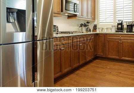 Stainless Steel Appliances in New Kitchen with Wood Floor and Cabinets