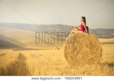 Beautiful girl sitting on a hay bale in the countryside