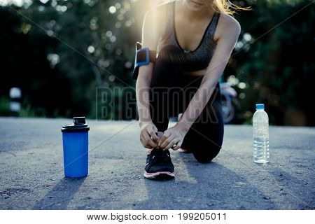 Young girl asian knelt down to do up his shoelaces on street after running exercise with protein shake and water bottle