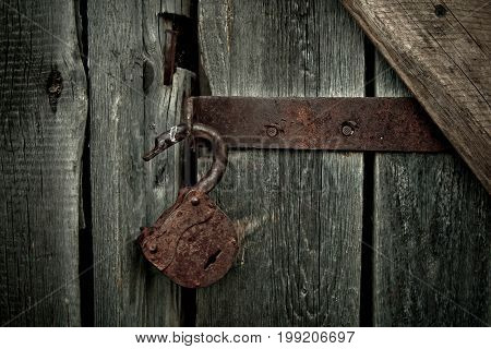 Old rusty opened lock without key. Vintage wooden door close up concept photo.