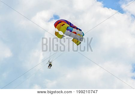 Colored Parasail Wing In The Blue Clouds Sky, Parasailing Also Known As Parascending Or Parakiting