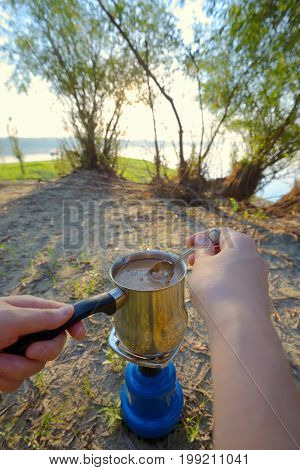 Making coffee on campfire in morning time