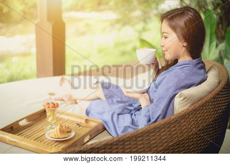 Asian girl sitting in the morning drinking coffee in a happy nature.