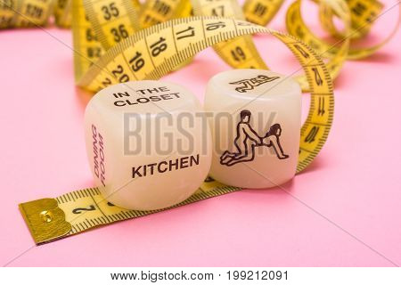 Sex for weight loss. Measuring tape and dice with poses of kamasutra sex toys.