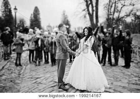 Gorgeous Wedding Couple Holding Hands On The Pavement While Crowd Of Kids Takes Pictures Of Them. Bl
