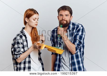 Young beautiful woman with a bearded man holding construction tools for repair on a light background.