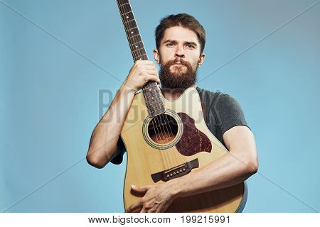 A man with a beard holds a guitar on a light blue background, a musician, musical instruments.