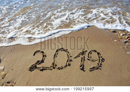 The inscription on the sand - 2019, the new year. Background.