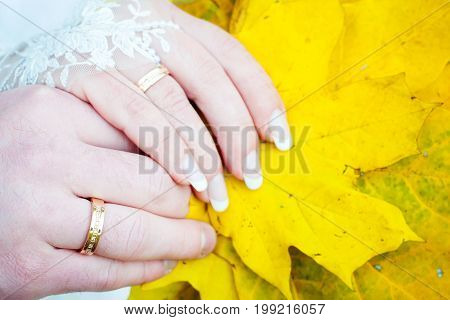 Fall engagement couple golding hands with leaf and diamond engagement ring