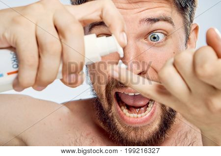 Man with a beard on white isolated background applies cosmetic cream, portrait, emotions.
