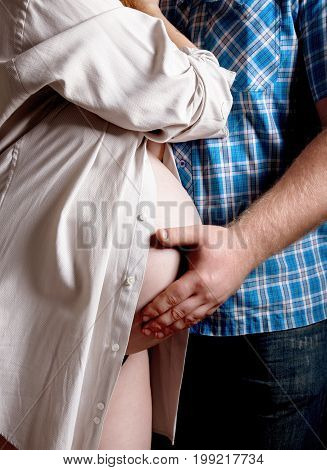 beautiful pregnant woman and her handsome husband hugging the tummy
