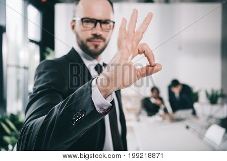 Handsome Young Businessman Showing Okay Sign With Blurred Colleagues On Background