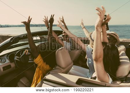 multicultural friends with outstretched arms riding car together at seaside