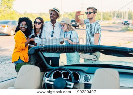 multiethnic group of friends use map to determine direction while standing near car together