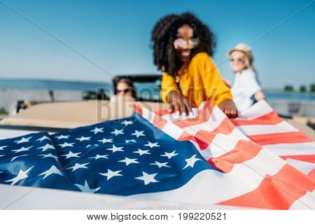 selective focus of multiethnic young women resting in car with american flag at seaside