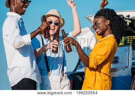 multiethnic cheerful friends drinking beer while spending time together