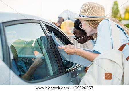 side view of multiethnic hitchhiking friends with map asking car driver destination