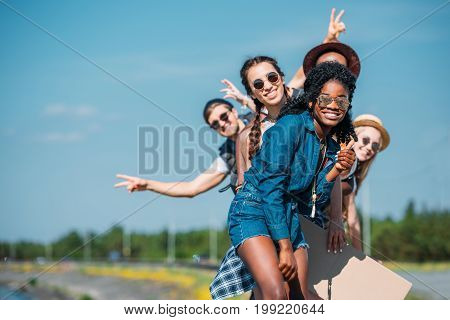 multiethnic happy young friends in casual clothing looking at camera
