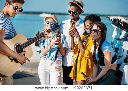 multiethnic group of friends drinking beer while spending time together at seaside