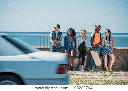 Multicultural Group Of Young People With Empty Cardboard Standing A Parapet While Hitchhiking Togeth