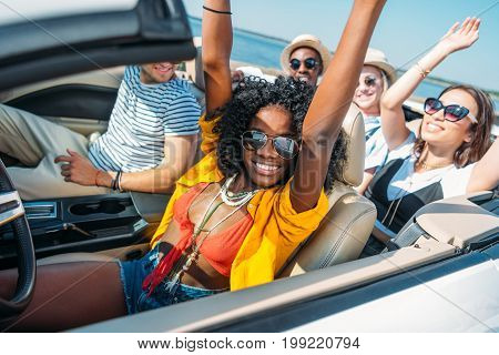 Multiethnic Smiling Friends Riding Car While Traveling Together