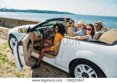 multicultural young friends sitting in car and looking at camera at seaside