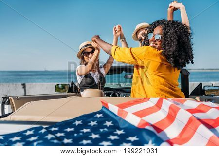 Multiethnic Women Holding Hands While Sitting In Car With American Flag At Seaside