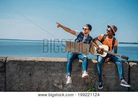 Multicultural Young Men Resting On Parapet While Hitchhiking During Trip