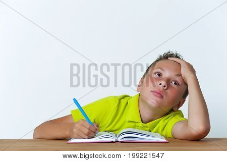 Tired 12 years old boy sitting at the table with exercise book and pen. School education.