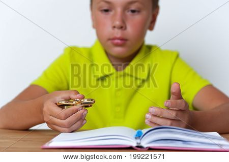 12 years old boy sitting at the table with exercise book and holding fidget spinner toy. School education concept.