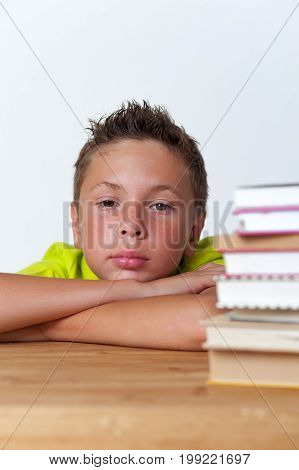 Portrait of 12 years old boy sitting at the table with books, trying to do homework lessons. Education concept.