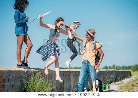 multiethnic group of young friends jumping of parapet together