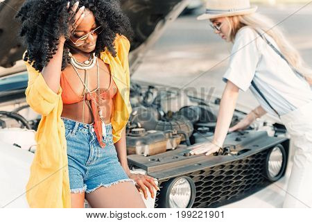 Multiethnic Women Standing Near Broken Car During Trip