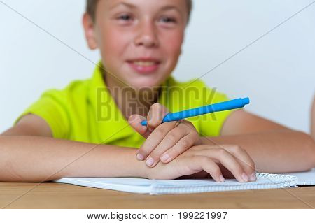 Portrait of happy smiling caucasian tween boy sitting at the table and doing homework. Education concept. Shallow depth of field