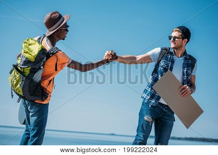 Side View Of Multicultural Young Cheerful Hitchhikers Shaking Hands