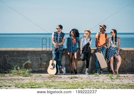 multicultural group of young people with empty cardboard standing a parapet while hitchhiking together