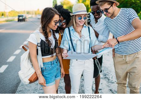 Multiethnic Group Of Friends Looking For Destination On Map While Traveling Together